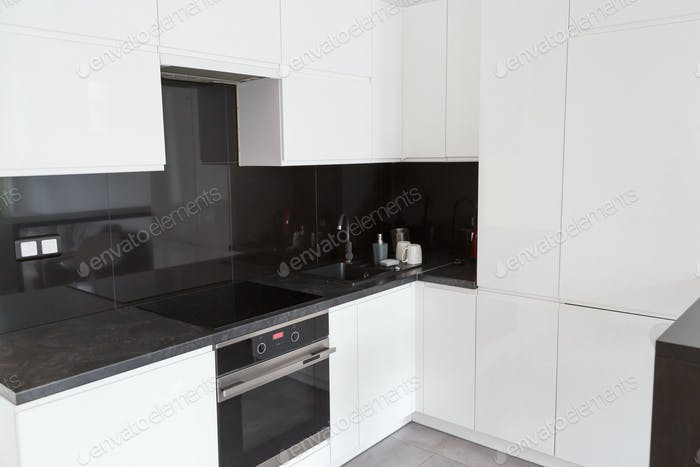 White kitchen with flat facades and black skinali.