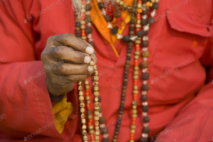 Close up of person wearing red robe and bead necklaces.