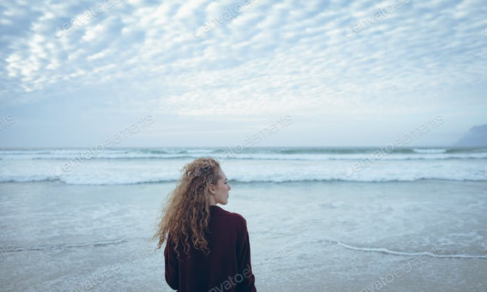 Woman with curly hair standing with face towards the sea at beach