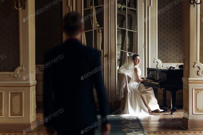 Красивый жених смотрит на свою великолепную невесту, играющую на фортепиано