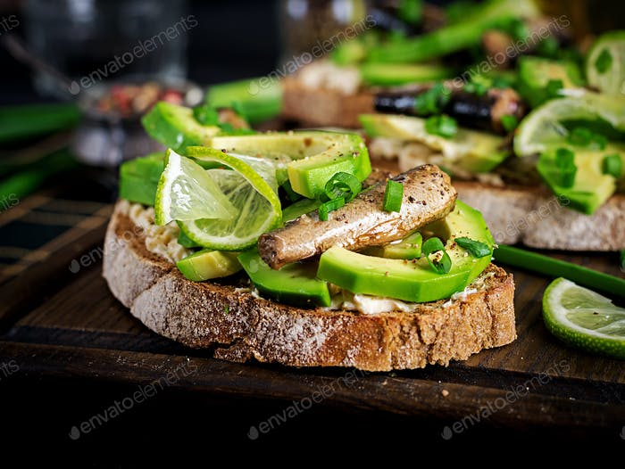 Sandwich - smorrebrod with sprats, avocado and cream cheese on wooden board. Danish cuisine.