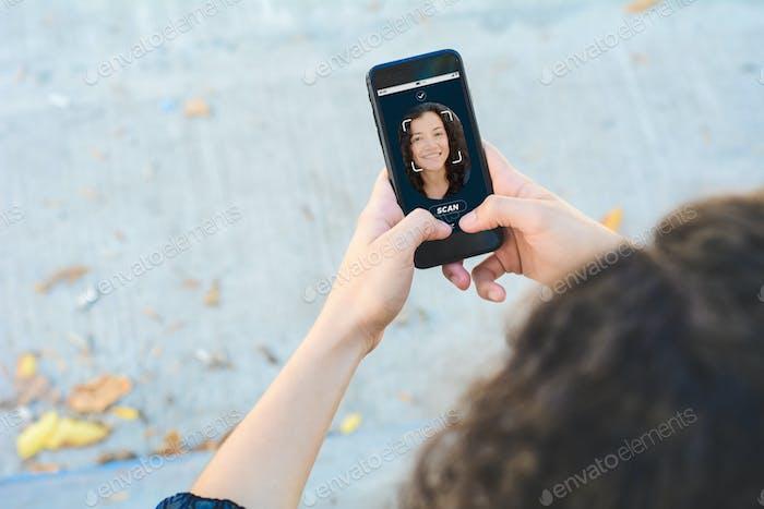 Smartphone de desbloqueo de mujer con tecnología de reconocimiento facial