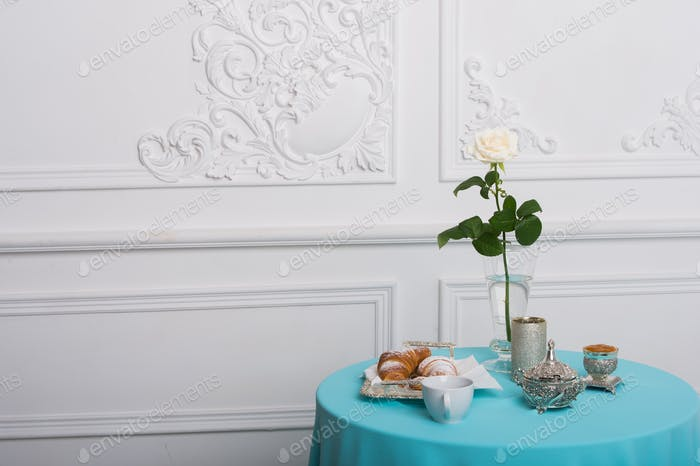 croissant and white rose on a table against luxury wall, copy space