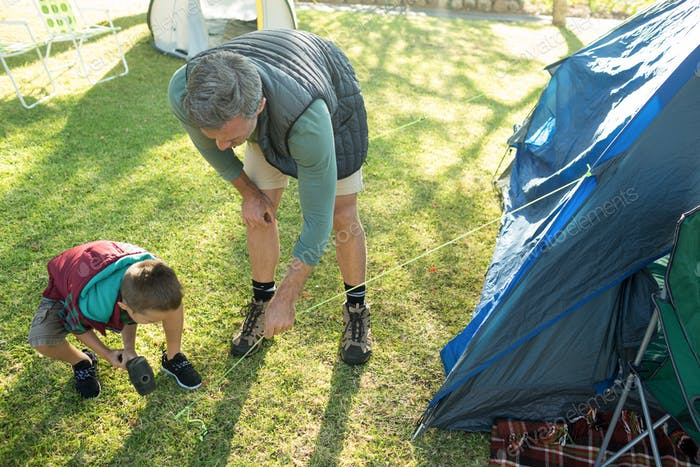 Father and son setting up the tent