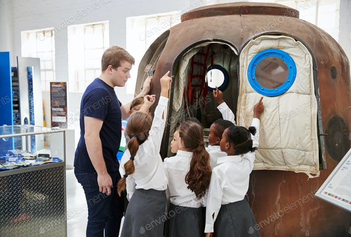 Kids and teacher look at a space capsule at a science centre
