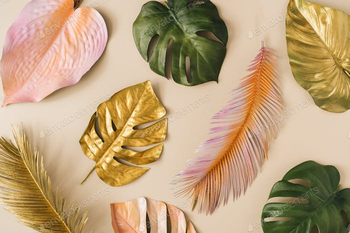Creative layout made of colorful and golden tropical leaves and palms. Minimal summer exotic