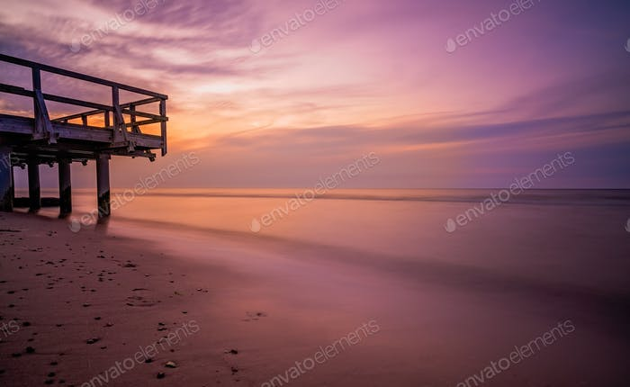 Sunset over wooden pier on the sea beach