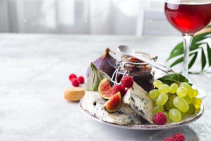 delicadeza quesos azules, fruta y mermelada en tarro con vino tinto en copa