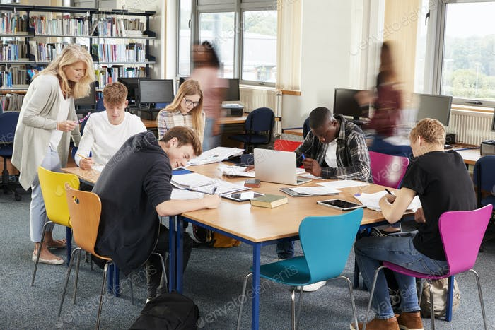 Busy College Library With Teacher Helping Students At Table