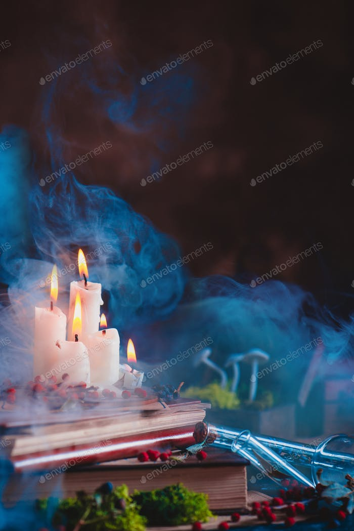 Burning candles with rising smoke in a magical still life with moss and mushrooms.