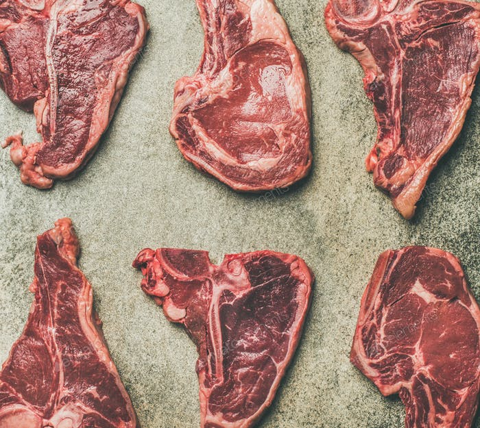 Flat-lay of fresh raw beef meat steaks, grey background