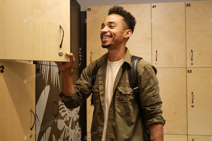 Young attractive casual African American man happily opening locker in office cloakroom