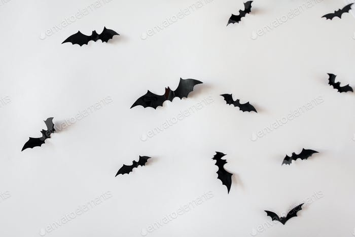black paper bats over white background