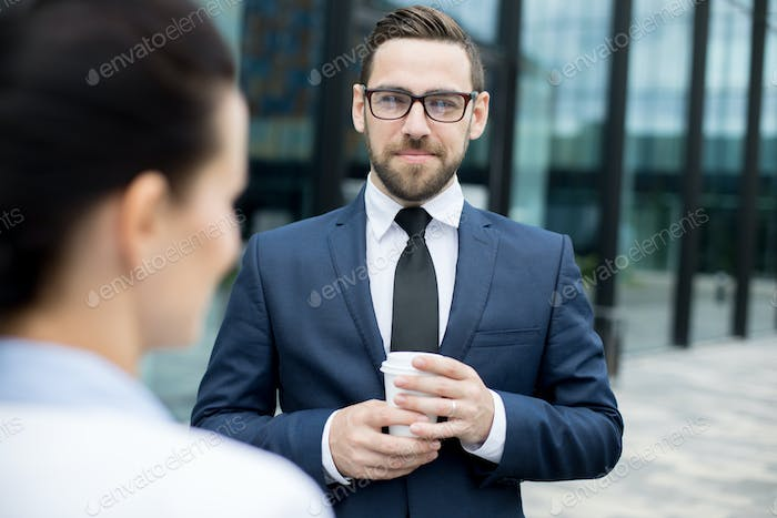 Man holding cup of hot drink behind woman