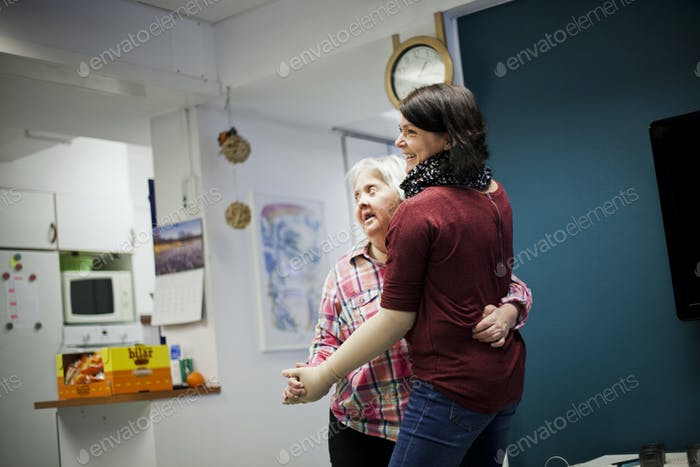 Mentally challenged woman dancing with caregiver at home