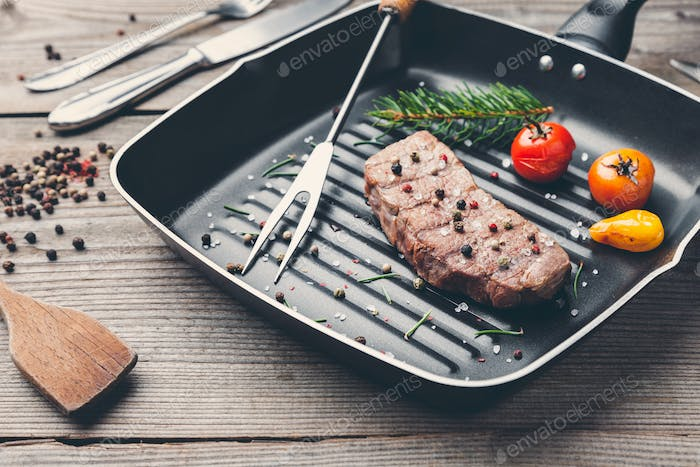 Delicious grilled steak with seasoning on wooden background