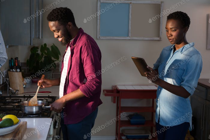 Woman digital tablet while man cooking in kitchen