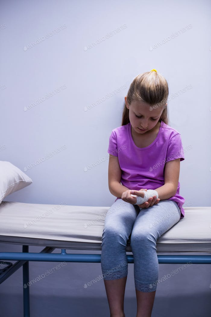 Girl with injured hand sitting on stretcher bed