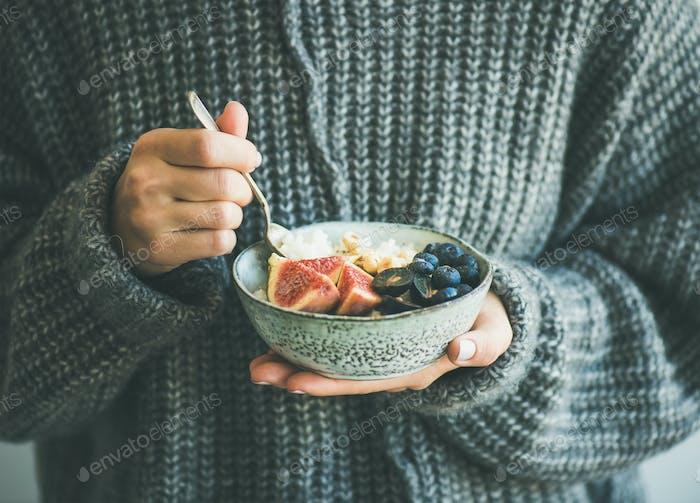 Woman in grey woolen sweater eating rice coconut porridge