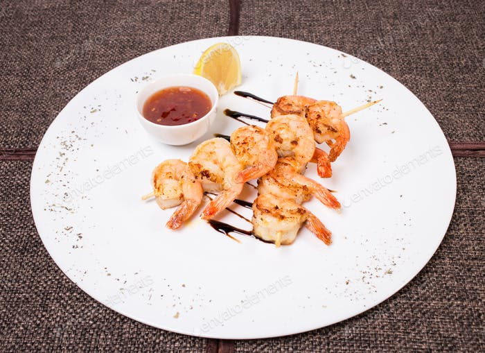 Delicious grilled shrimps on skewers.