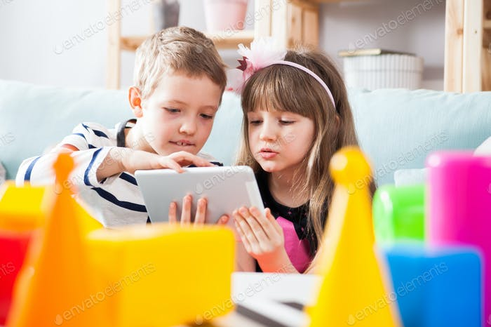 Siblings sitting on sofa at home and playing with pc tablet together