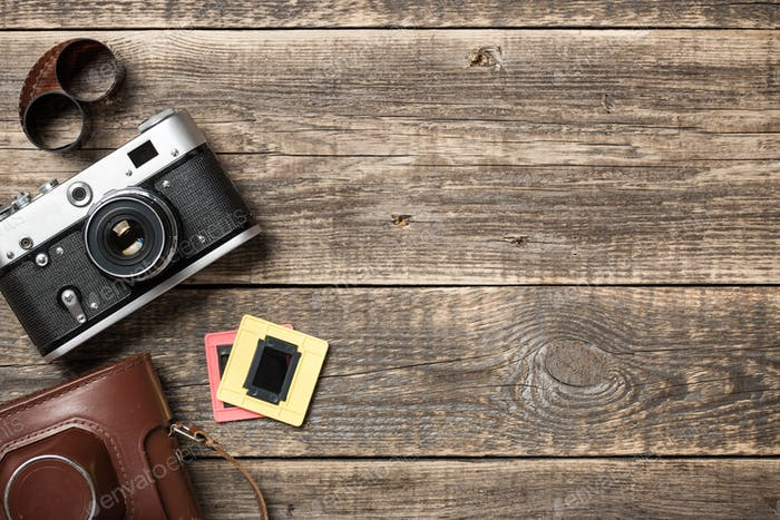 Retro camera and roll film on wooden background