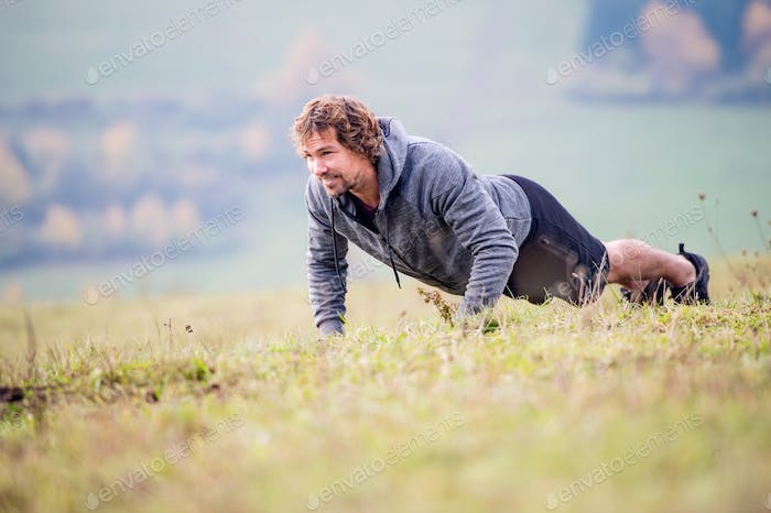 Handsome young runner doing push ups, autumn nature