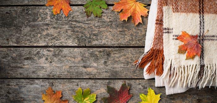 Herbsthintergrund mit Plaid und Blättern