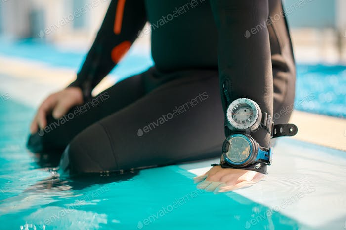 Male diver in scuba gear sitting at the poolside