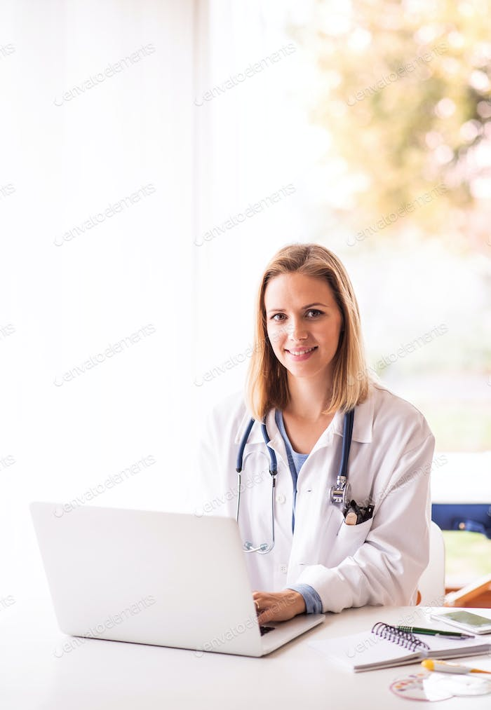 Female doctor with laptop working at the office desk.