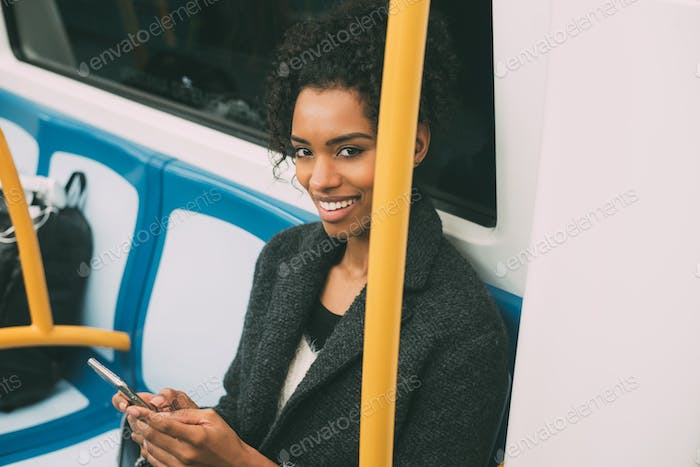 Happy young black woman sitting inside the underground on the mobile phone