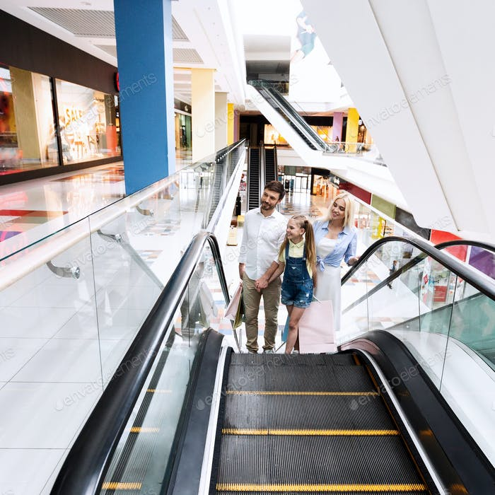 Family On Shopping Moving Up On Escalator Stairs In Hypermarket