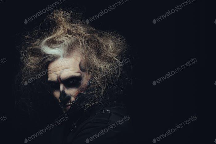 Skull makeup portrait of young man. Halloween face art.