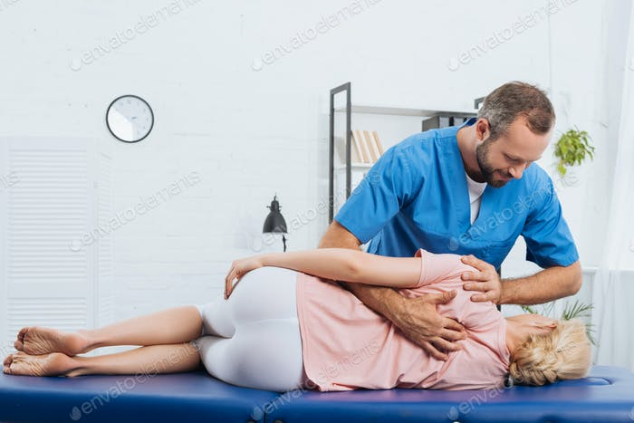 smiling chiropractor massaging back of patient that lying on massage table in hospital