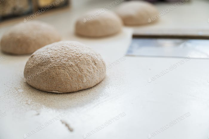 Fresh dough for bread buns resting and rising on kitchen counter