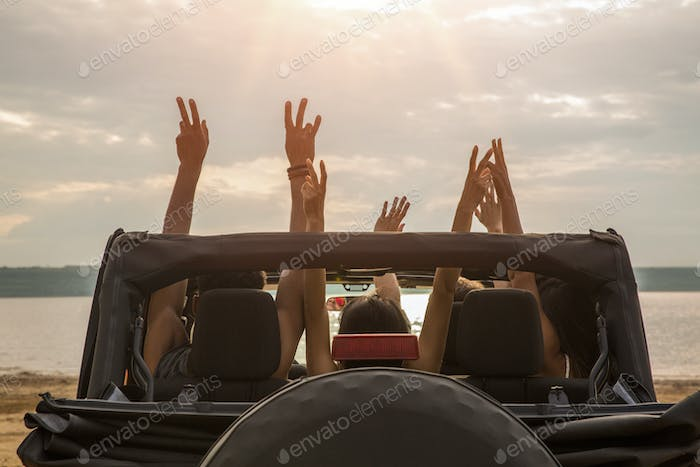 Friends sitting in a car with hands raised