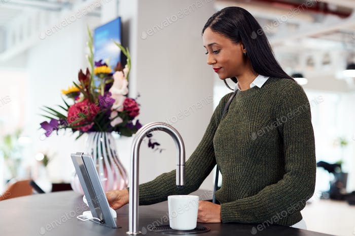 Businesswoman Getting Hot Drink From Automated Dispenser In Office