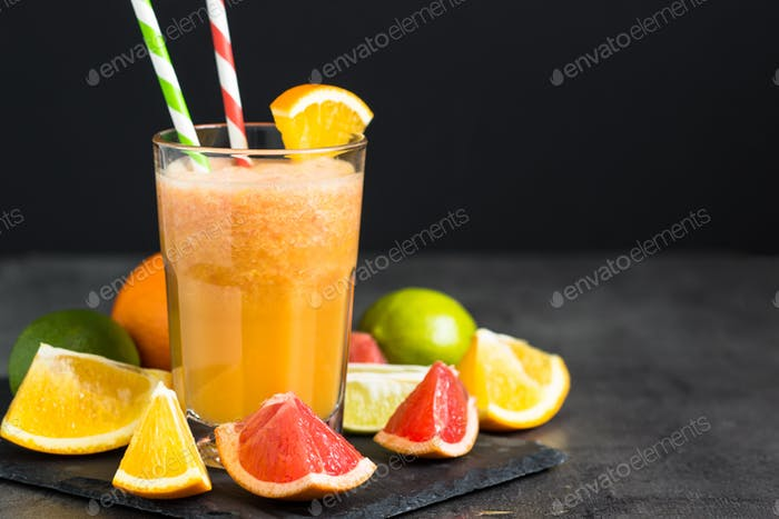 Fresh citrus smoothie juice at dark background.