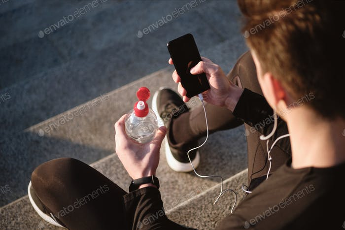 Close up of sporty man with bottle of water using cellphone outdoor