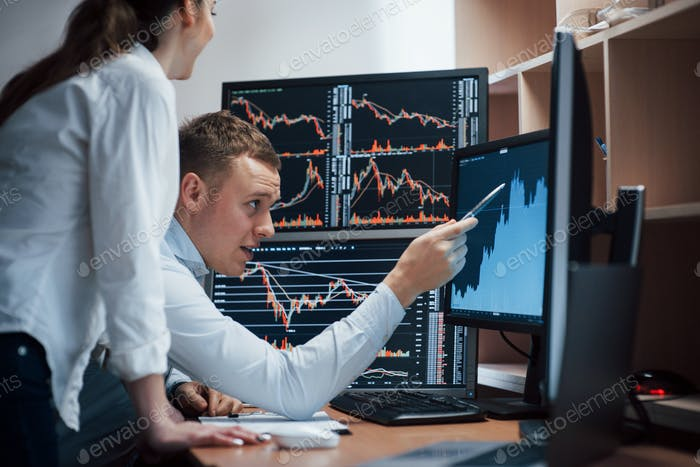 Team of stockbrokers are having a conversation in a office with multiple display screens