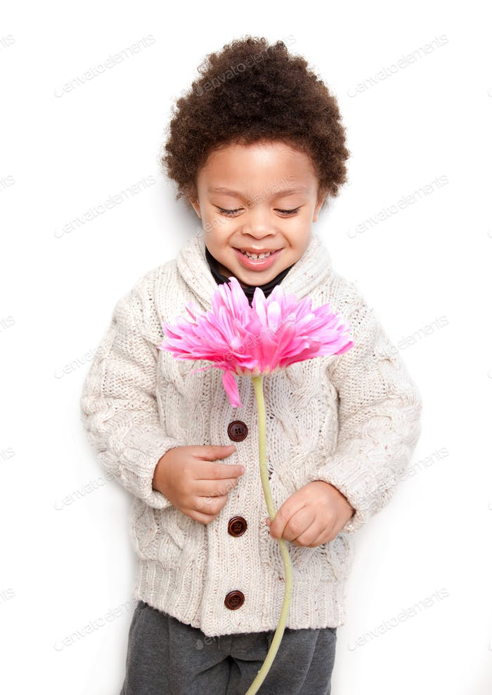 Cute child holding a big pink flower and looking at it