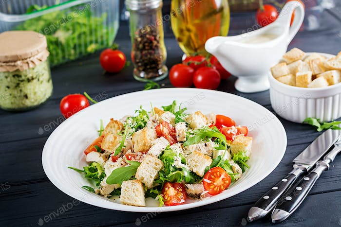 Healthy grilled chicken Caesar salad with tomatoes, cheese and croutons. North American cuisine.