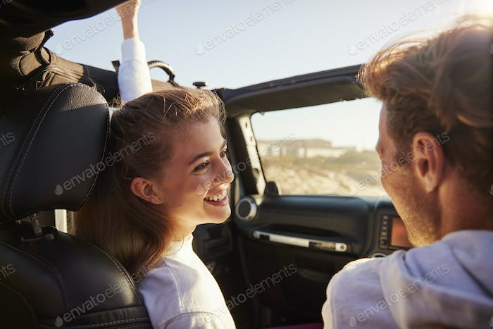 Couple look at each other while driving, rear passenger POV