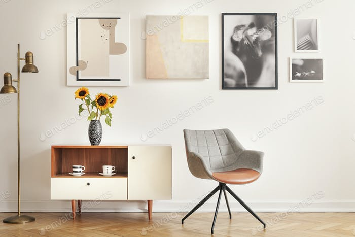 Grey armchair next to cupboard with sunflowers in white room int