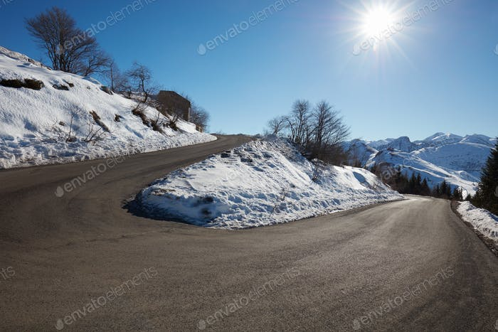 Empty mountain road curve with snow on sides, blue sky and sun