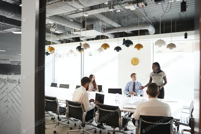Businesswoman Giving Boardroom Presentation Viewed Through Meeting Room Door