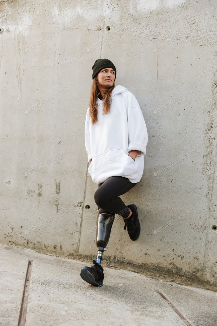 Photo of caucasian disabled girl with bionic leg in casual wear,