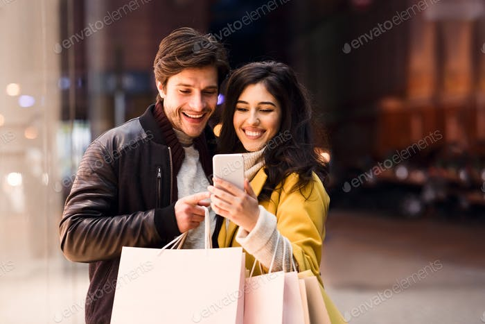 Happy couple ordering taxi on cellphone, walking near city center