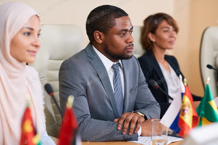 Serious young African-american speaker listening to one of foreign colleagues