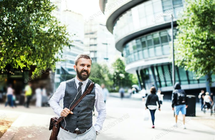 Hipster businessman with earphones walking on the street in London.